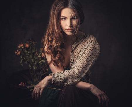 Aging and skin care concept. Half old half young woman with faded rose bouquet.