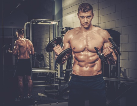 Athletic man doing exercises with dumbbells in The Gym's Studio Stock Photo - 52913726
