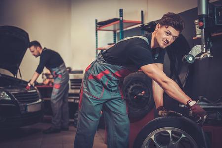 mécanicien automobile professionnel équilibrage roue de voiture sur équilibreur en service de réparation automobile. Banque d'images