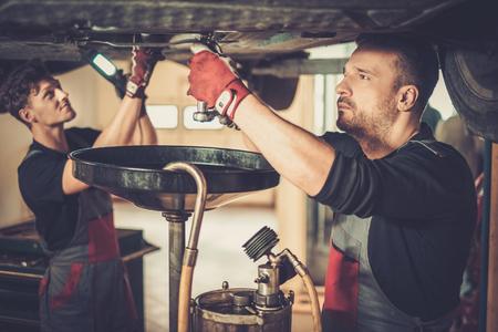 Profecional automonteur veranderende motorolie in auto-motor op onderhoud, reparatie tankstation in een auto workshop.
