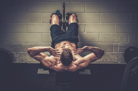Muscular man doing exercises for abdominal in The Gym's Studio Stock Photo - 52898944