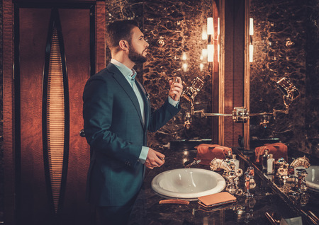 Confident well-dressed man using perfume in luxury bathroom interior. Stock Photo - 53532944