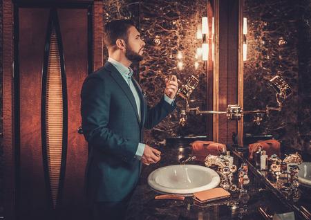 Confident well-dressed man using perfume in luxury bathroom interior.