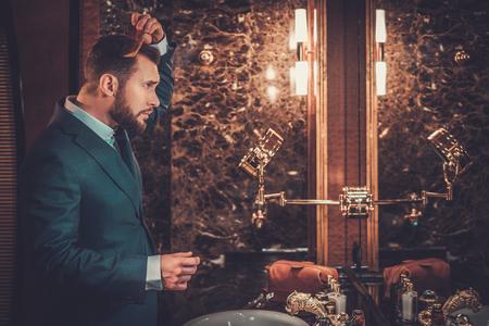 Confident well-dressed man combing hair in luxury bathroom interior.
