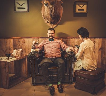 위스키의 유리는 이발소에서 남성 매니큐어를하고 자신감 구식 남자.