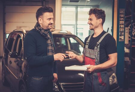 Professional car mechanic giving client keys to his repaired car in auto repair service.