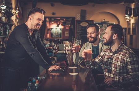 Vrolijke oude vrienden drinken bier van het vat op bar in pub. Stockfoto