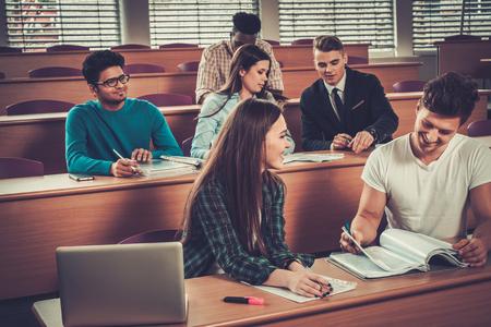 Multinationale groep van vrolijke studenten actief deel te nemen in een les zittend in een collegezaal.