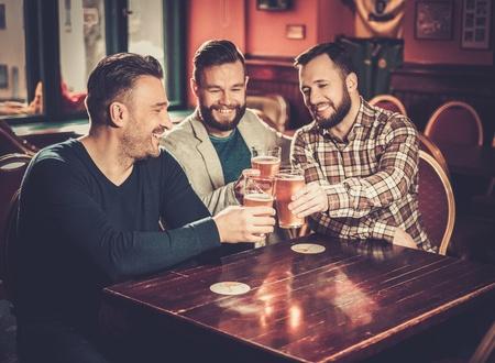 Cheerful old friends having fun and drinking draft beer in pub. Zdjęcie Seryjne