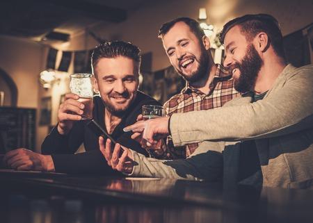Alegres viejos amigos divirtiéndose con smartphone y bebiendo cerveza de barril en barra de bar en pub.