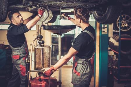 mécanicien automobile Profecional changement d'huile moteur dans le moteur de l'automobile à la station de service de réparation et d'entretien dans un atelier de voiture. Banque d'images