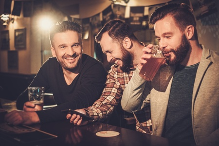 Cheerful old friends having fun with smartphone and drinking draft beer at bar counter in pub. Stock Photo - 53741613