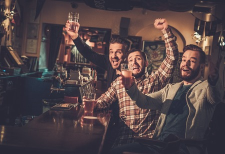 Cheerful old friends having fun watching a football game on TV and drinking draft beer at bar counter in pub. Stockfoto