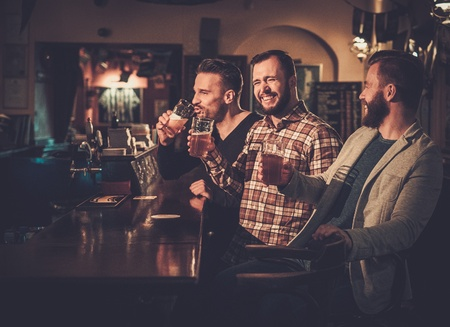Cheerful old friends having fun and drinking draft beer at bar counter in pub. Stockfoto