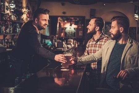 Cheerful old friends drinking draft beer at bar counter in pub. Zdjęcie Seryjne
