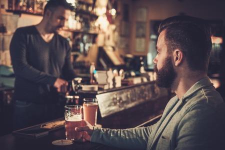 estilo del hombre sentado solo en barra de bar con una pinta de cerveza ligera.