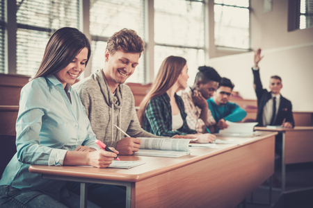 grupo multinacional de estudiantes alegres que toman parte activa en una lección mientras está sentado en una sala de conferencias.