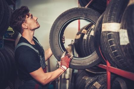 meccanico di auto professionale scegliendo nuovo pneumatico in servizio di riparazione auto. Archivio Fotografico