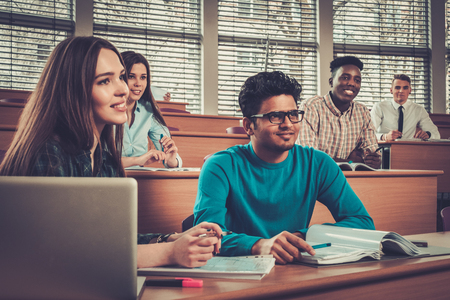Wielonarodowa grupa wesołych studentów biorących aktywny udział w lekcji, siedząc w sali wykładowej.