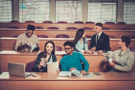 gruppo multinazionale di studenti allegri che prendono parte attiva in una lezione, seduti in una sala conferenze.