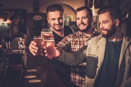 Vrolijke oude vrienden plezier en het drinken van bier van het vat op bar in pub. Stockfoto