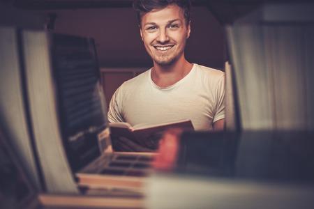 Portrait d'un étudiant souriant sur la bibliothèque à la recherche d'un livre à la bibliothèque.