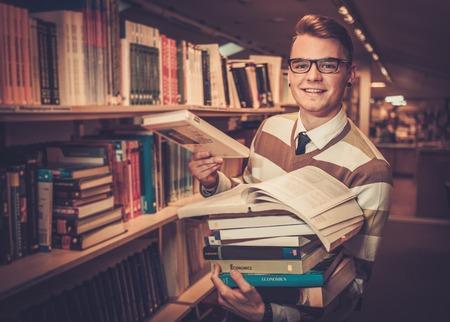 대학 도서관에서 책의 더미를 보유하는 젊은 매력적인 사서.
