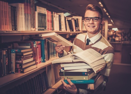 Young attractive librarian holding a pile of books in the university library. Standard-Bild