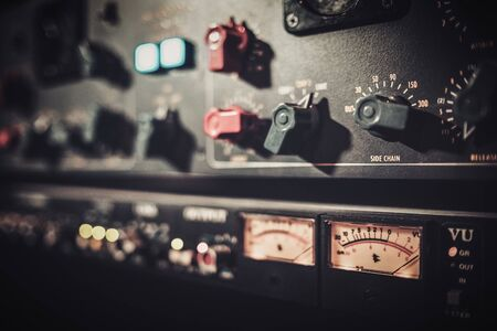 Close-up amplifier equipment with sliders and knobs at boutique recording studio. Stock fotó