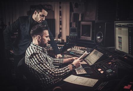 사운드 엔지니어와 프로듀서는 부티크 녹음 스튜디오에서 패널을 혼합 함께 작동합니다.