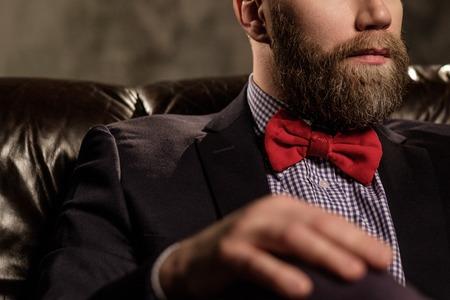 グレーに分離された快適な革のソファに座っている昔ながらの髭の男。 写真素材
