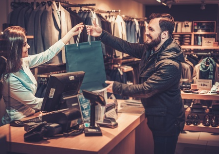 Happy handsome man taking shopping bag from saleswoman in a suit shop. Stockfoto