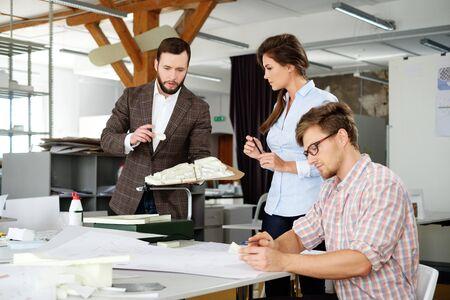 Confía en equipo de ingenieros que trabajan juntos en un estudio de arquitectura.