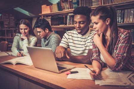 Wielonarodowa grupa wesołych studentów studiujących w bibliotece uniwersyteckiej.