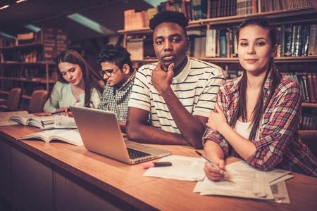 grupo multinacional de estudiantes alegres que estudian en la biblioteca de la universidad.
