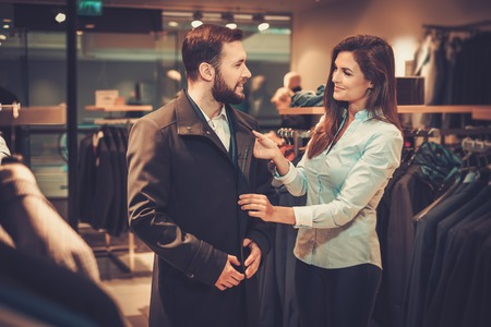 Confident handsome man with beard choosing a coat in a suit shop. Banco de Imagens
