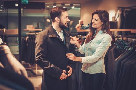 Zekere knappe mens die met baard een laag in een kostuumwinkel kiest.