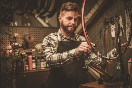 Stylish bicycle mechanic doing his professional work in workshop.