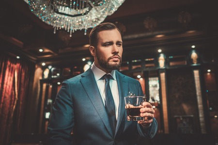 Confident well-dressed man with glass of whisky in luxury apartment interior.
