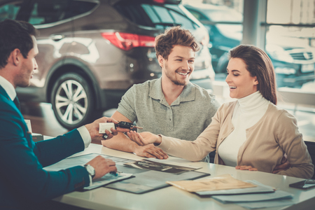 Salesman giving the key of the new car to a young couple at the dealership showroom.