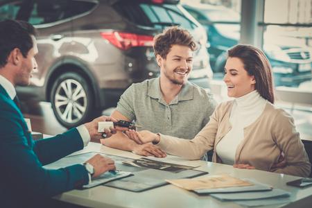 Verkoper het geven van de sleutel van de nieuwe auto op een jong paar bij de dealer showroom.