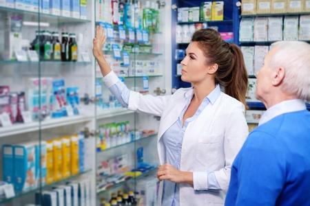 아름 다운 젊은 여자 약사 수석 사람이 약국에서 고객에 게 마약을 표시합니다.
