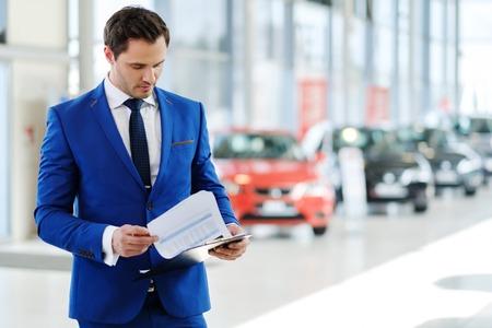 Confident young car dealer standing in showroom. Standard-Bild
