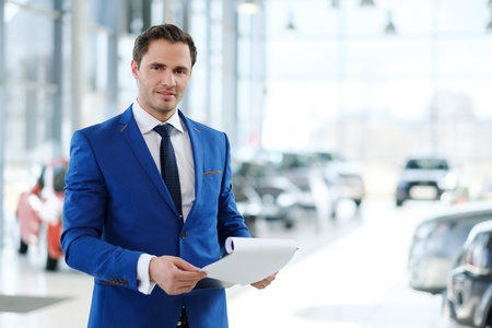 Confident young car dealer standing in showroom. Stockfoto