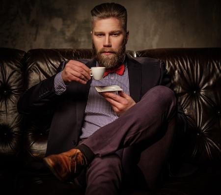 Altmodische bärtiger Mann in bequemen Ledersofa mit einer Tasse Kaffee auf grau isoliert sitzen.