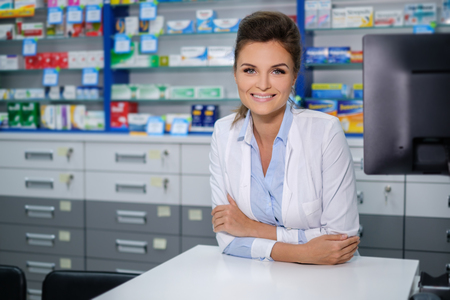 Portrait of beautiful smiling young woman pharmacist standing in pharmacy. Standard-Bild