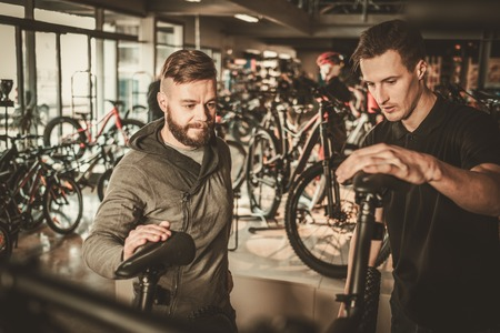 Salesman showing a new bicycle to interested customer in bike shop.