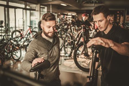 Verkoper met een nieuwe fiets aan geïnteresseerde klanten in fietsenwinkel.