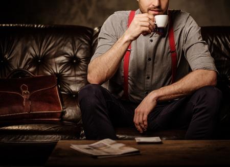 Junge gut aussehend altmodischen bärtiger Mann mit einer Tasse Kaffee auf bequemen Ledersofa auf dunklem Hintergrund sitzt.