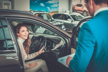 Piękna młoda kobieta kupuje samochód w salonie dealerskim. Zdjęcie Seryjne